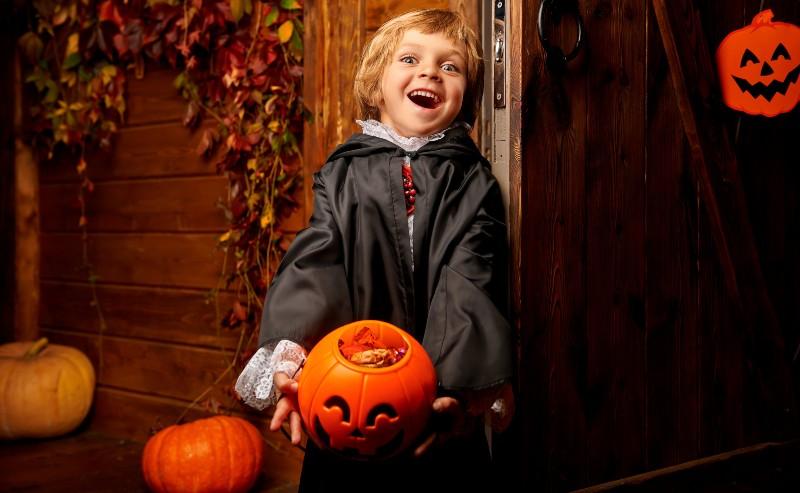 un petit garçon avec un déguisement Halloween qui porte un sceau en forme de citrouille plein de bonbons