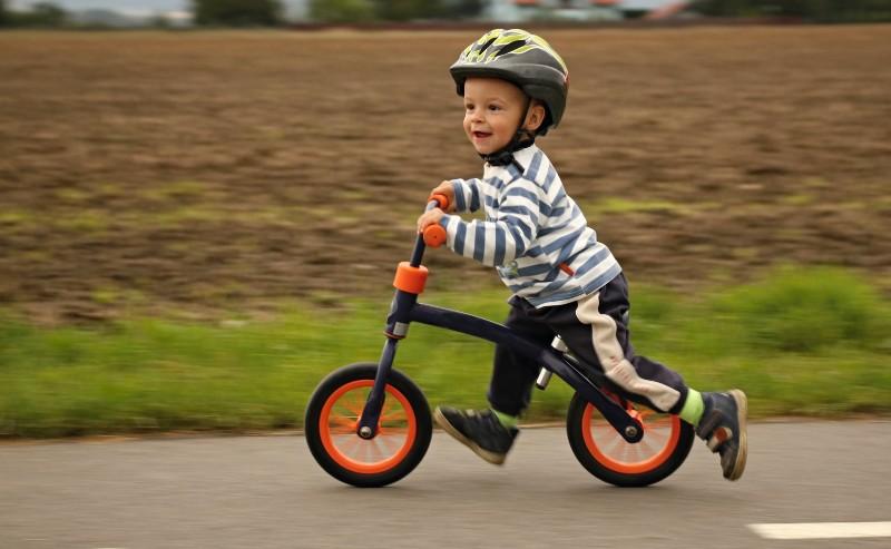 Jeune enfant faisant de la Draisienne garçon sur route
