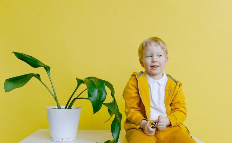 enfant assis près d'une plante verte habillé d'un survêtment garçon