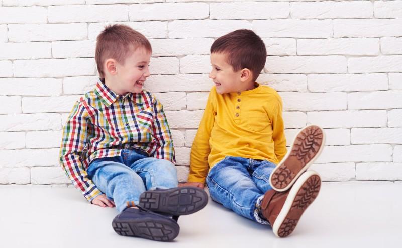 deux enfants assis sur le sol se gardant tout en souriant habillés avec des vêtements de garçons