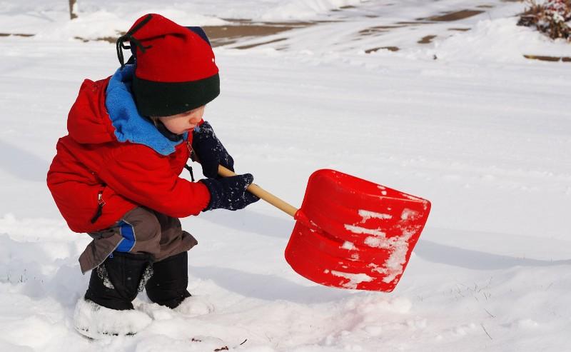 adorable petit garçon qui joue dans la neige equipé d'une doudoune rouge et d'une paire de botte de neige garçon