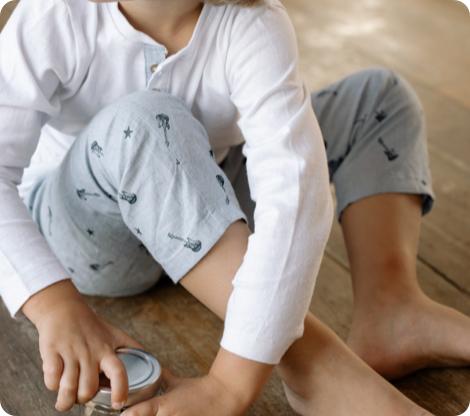 Enfant en pyjama assis sur le sol et qui ouvre une boîte de conserve