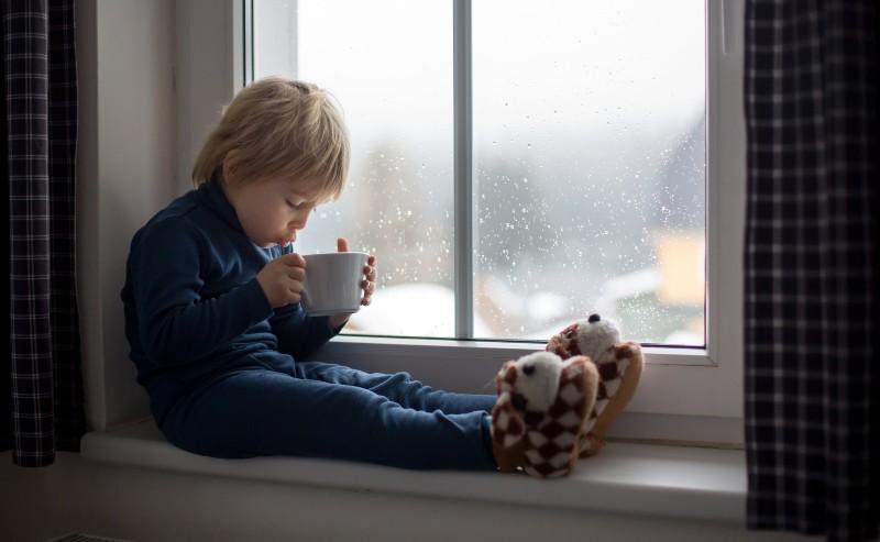 enfant assis près d'une fénêtre buvant un chocolat chaud et portant des chausson garçon