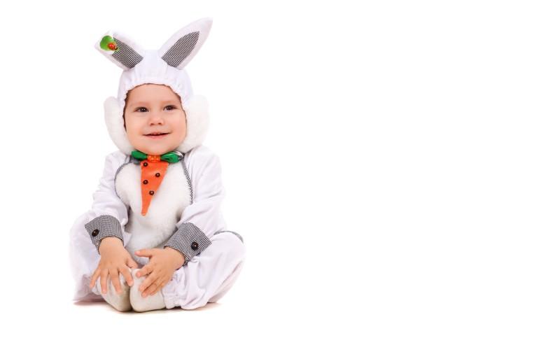 un bébé avec un déguisement bébé garçon lapin assis sur le sol
