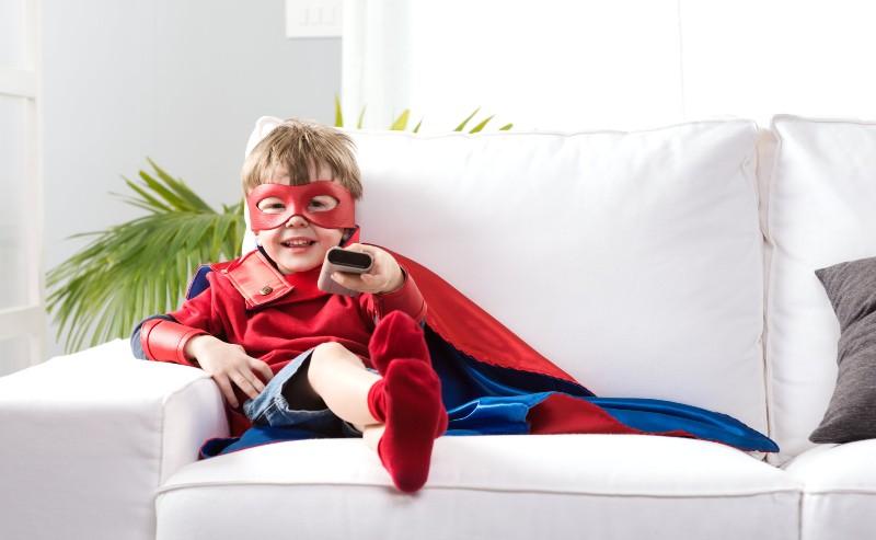 petit garçon assis sur un canapé blanc et une télécommande à la main avec un déguisement garçon