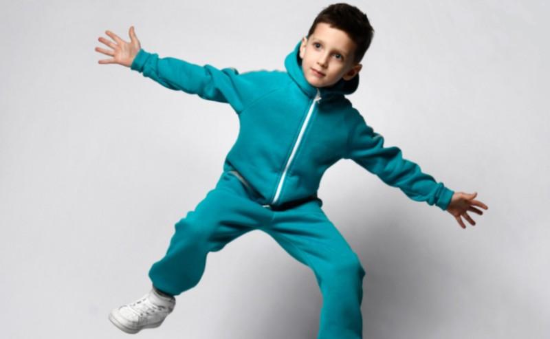 un petit garçon sautant en l'air portant un jogging garçon
