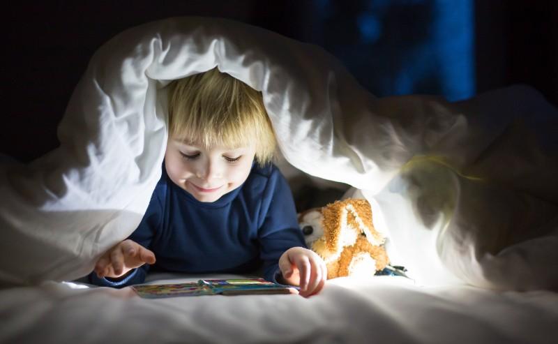 petit garçon lisant sous sa housse de couette garçon