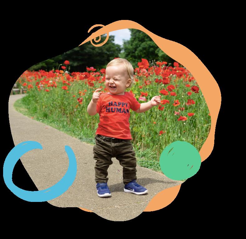 bébé qui se promène sur une route proche d'un champ de fleur