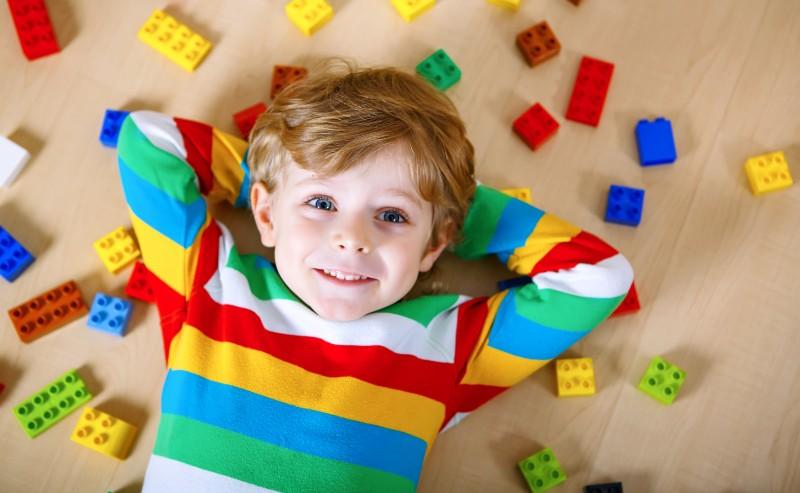 enfant avec un pull rayé de plusieurs couleurs allongé avec des jeux garçon