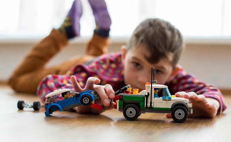 enfant allongé sur le sol jouant avec un jouet garçon