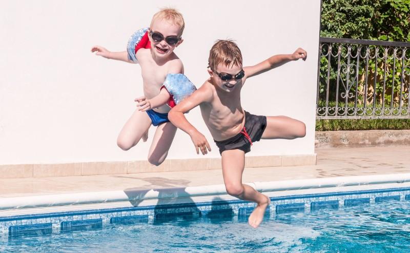 deux jeunes enfants qui portent un maillot de bain garçon sautant dans une piscine