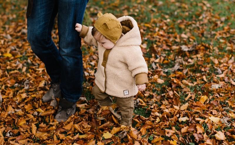 petit garçon qui donne la main à son papa pendant une balade en forêt portant un manteau garçon