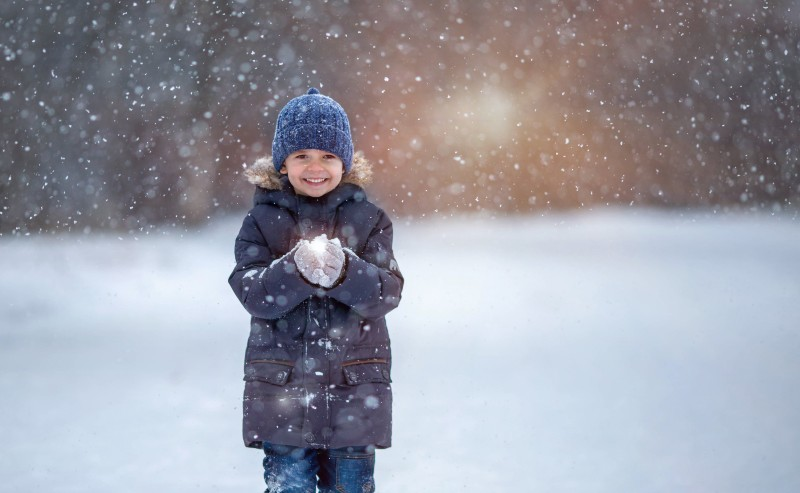 enfant souriant sous la neige portant une parka garçon