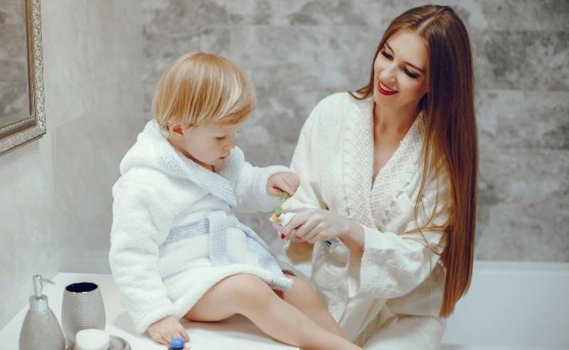enfant portant un peignoir garçon avec sa maman dans une salle de bain
