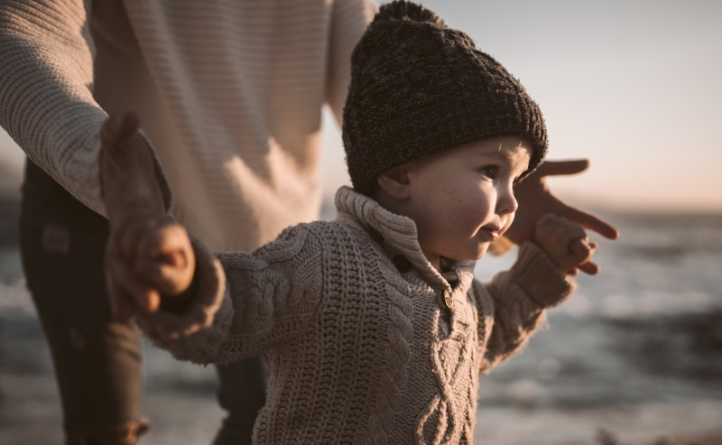 enfant portant un pull garçon au bord de la plage avec son papa