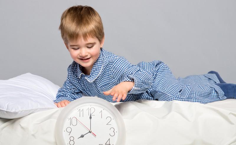 enfant allonger sur son lit en pyjama à carreaux