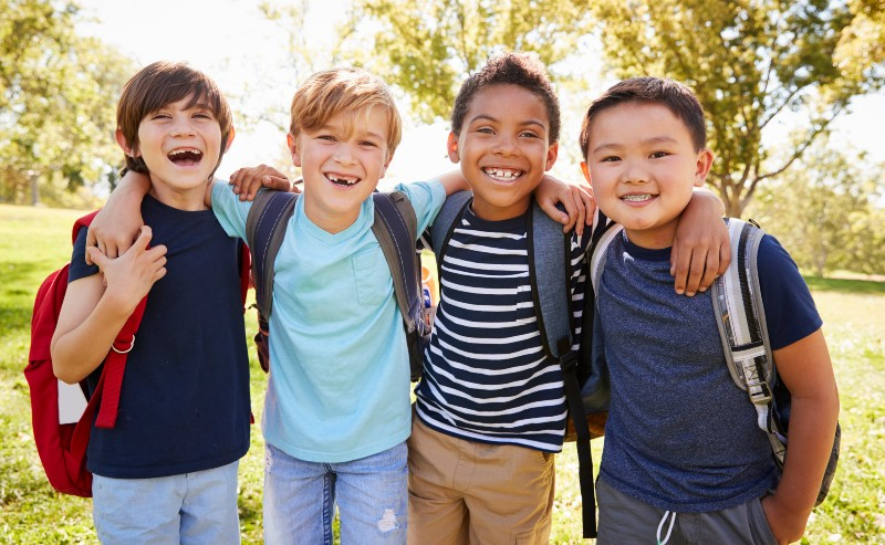 quatre écoliers souriant portant des sac à dos garçon