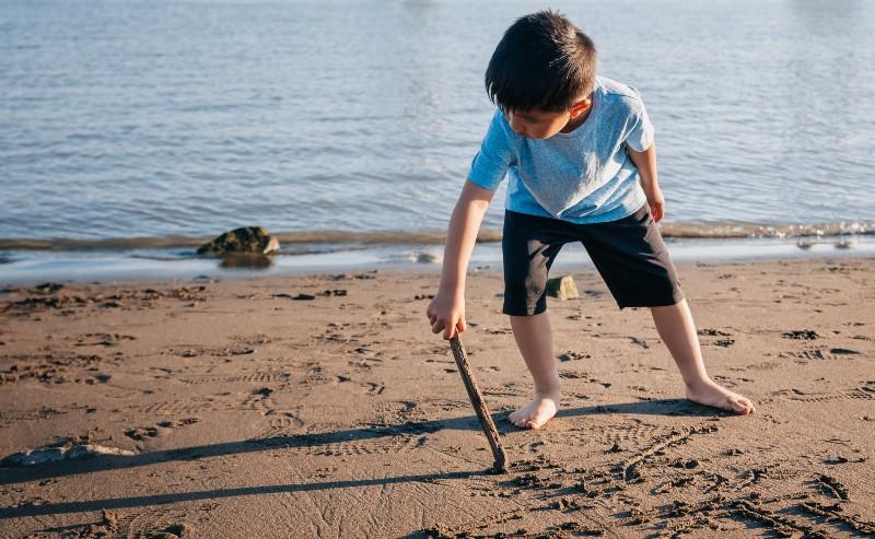 enfant qui joue sur la plage portant un short garçon