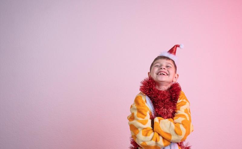enfant souriant habillé d'un surpyjama garçon et 'une guirlande rouge autour du cou