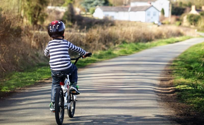 enfant qui fait du vélo garçon sur une route de campagne